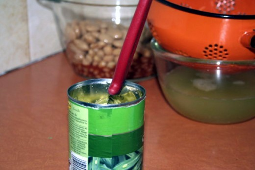 With a sharp knife cut the beans in the can. Slide the knife with the blade at 90 degrees, sharp side facing the opposite side of the can. Slice across, then move the knife to midway and repeat, do this several times.  Then drain and add to mixing bo