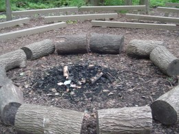 An acrid smell of old campfire and coals.
