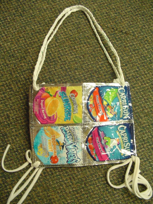 A plastic handbag made by local students from repurposed drink pouches packets