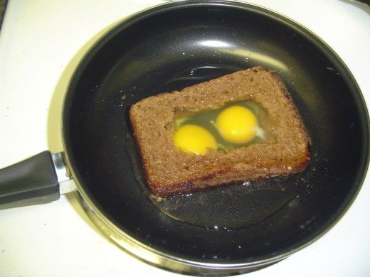 Two eggs are broken and added to the middle of the sandwich. The sandwich is cooked at low heat for about 7 minutes before turning