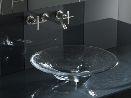 A elegant clear bathroom basin with wall mounted faucet. A clean bathroom sink basin could be visually clean and yet not be sanitized.