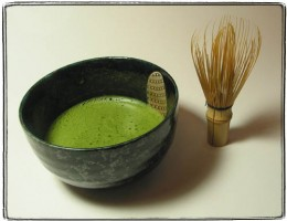 frothy green matcha with a bamboo whisk