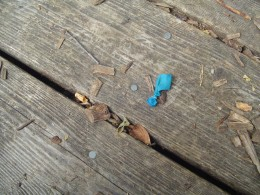 A bright blue baloon next to metal nails.