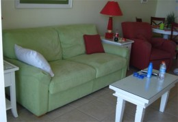 Pull-out sofa couch, coffee table, chair, and kitchen table in the back.