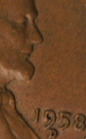 Close up of the face doubling from the nose to the bow tie, the 19 in the date are also doubled die.