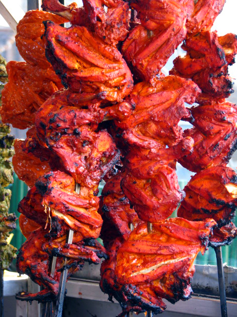Whole chicken marinated and half cooked with Tandoori masala hanging on skewers ready to be plunged into a hot Tandoor for a second time to finish the cooking process at a restaurant.