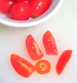 Grape tomato quartered, with end cut off, ready for black bean and corn salad. Photo by Sally's Trove.
