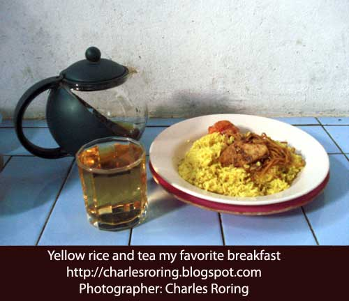 A plate of yellow rice with fried fish and tea that I ate this morning.