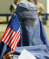A burkha clad Afghan woman holds a US flag at a ceremony in Kabul on Monday. The ceremony was organised by the Wheelchair Foundation, a US-based NGO, to mark the donation of over 5000 wheelchairs to Afghanistan. — Reuters