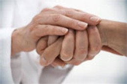 medical caregiver holding patient's hand