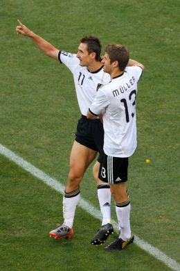 Miroslav Klose of Germany celebrates scoring the opening goal with team mate Thomas Mueller (R) during the 2010 FIFA World Cup South Africa. (June 26, 2010 - Photo by Cameron Spencer/Getty Images Europe)
