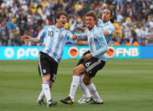 Gabriel Heinze of Argentina celebrates with teammates Lionel Messi (L) and Martin Demichelis (R) after he scores the opening goal during the 2010 FIFA World Cup South Africa Group B match between Argentina and Nigeria at Ellis Park Stadium on June 12