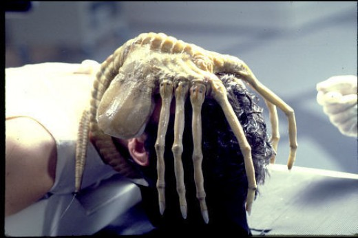 """John Hurt on a table in the film """"ALIEN"""" with the alien wrapped on his face. Removing it will kill him, yet it keeps him alive. His life depends on it. This is a good analogy for Banks as Predators and their manic need to survive at all cost."""