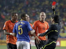 Referee Yuichi Nishimura flashes the red card to Brazil's Felipe Melo (5) for his foul on Netherlands' Arjen Robben (2nd R) during the 2010 World Cup quarter-final soccer match.