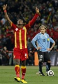 Uruguay's Diego Forlan,looks as Ghana's John Pantsil reacts to goal by Sulley Muntari- World Cup quarterfinal soccer match Friday, July 2, 2010. Photo -AP