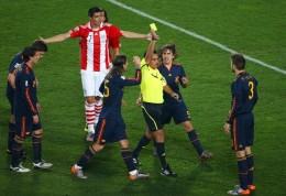 Referee Carlos Batres issues Gerard Pique of Spain with a yellow card after pulling down Oscar Cardozo of Paraguay in the penalty area during the 2010 FIFA World Cup South Africa Quarter Final match between Paraguay and Spain at Ellis Park Stadium on