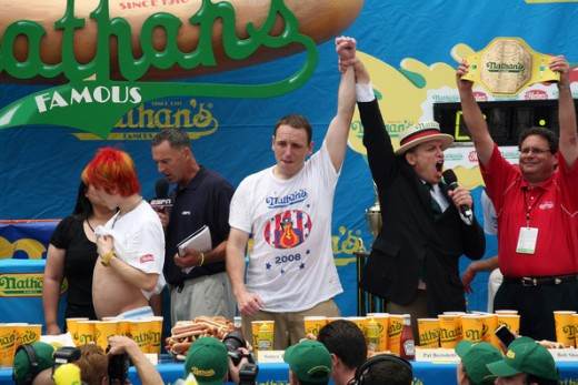 Image from 2008 Nathan's Hot Dog Eating Contest. Joey Chestnut is the middle being declared the winner by event organizer George Shea. Walking away in the red hair is Takeru Kobayashi, six time winner of the contest.