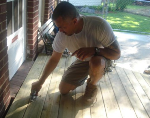 Scrubbing rough edges from a nealy built wood ramp; preparing for the stain.