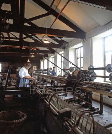 The industrial revolution began with the introduction of creating a surplus by extending productive capacity using machine power as in this weaving factory of a bygone era.