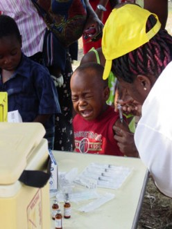 This Mozambique boy manages his measles 'jab' the best he can...