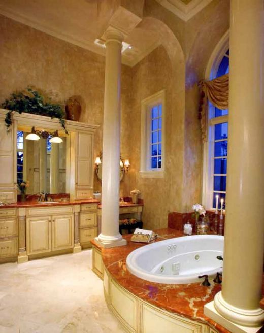 beautiful marble bathroom with cream, antique cabinets, high ceilings, pillars and various marble finishes throughout - elegant and impressive