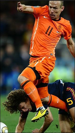 Netherlands' striker Arjen Robben gets by Spain's defender Carles Puyol .