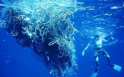 This image shows a diver in a diving team and a large collection of plastic floating free in the ocean.