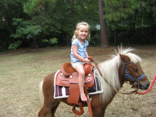 Audrie riding Snickers at Lexi's birthday party.