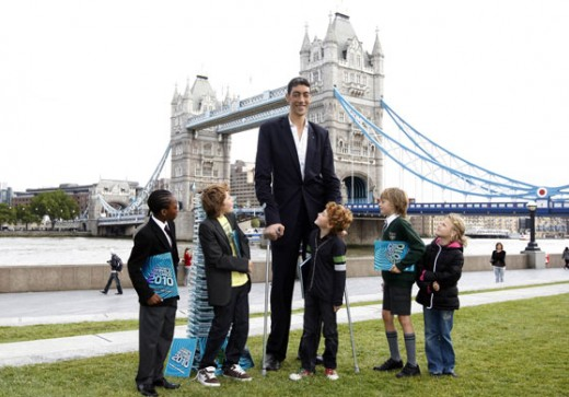 World's tallest man SULTAN KOSEN poses for school children during an event in London to promote the Guinness Book of World Records 2010 Book