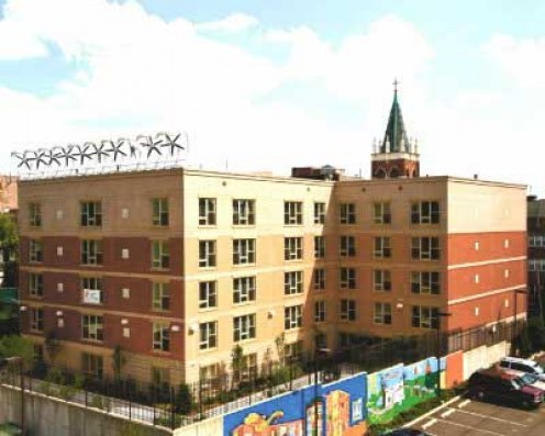 Micro wind turbines on an apartment building's roof help offset energy costs in the building.