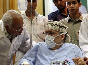 Freed Lockerbie bomber Abdelbaset Ali Mohmet al-Megrahi speaks to a doctor as he wears a medical and sits on a wheelchair