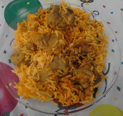 - Spread the cooked chicken curry over the rice in layers.       - Cover the pot and cook on low heat till the rice is completely done.      - Mix the biryani and serve with raita or salad.