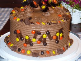 Reese's candy cake.  M&Ms and Reese's are perfect for borders.  The cups on top are just on wires that were covered with floral tape, curled around a pencil, and stuck into the cake.  The letters are dried chocolate fondant.