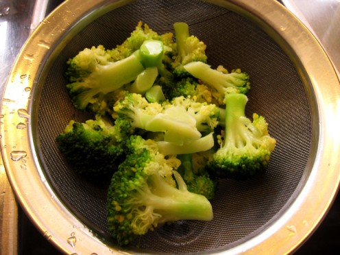 Blanched broccoli put in the strainer, after being washed in cold water.