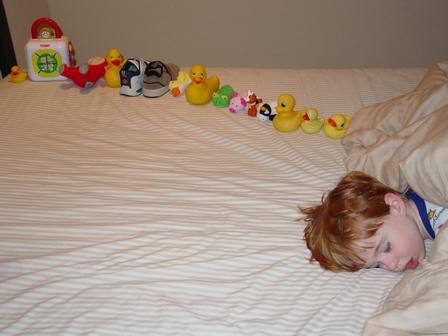 A child showing autistic behavior, by making a line of toys.