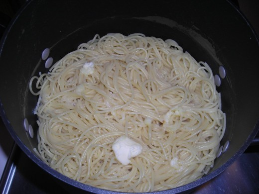 THE PREPARED SPAGHETTI TOPPED WITH BUTTER AND OLIVE OIL