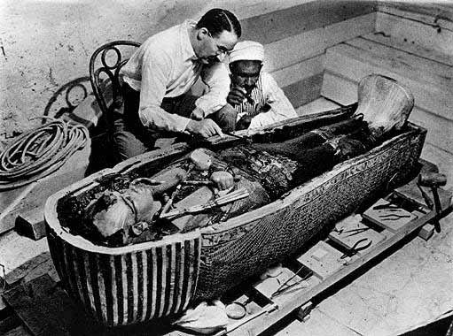 Howard Carter bending over the 2nd layer of the sarcophagus.