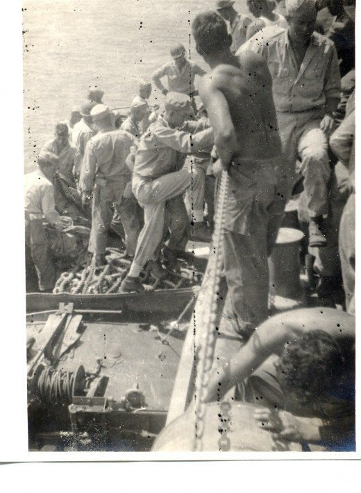 U.S. Army Soldiers boarding landing craft from troop ship during Philippine Campaign in WW II