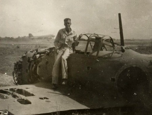 U.S. Army Staff Sargent Charles Nugent posing on wreckage of Japanese fighter plane at Clark Field in Philippine Islands during World War II