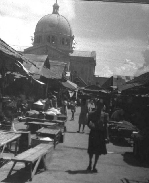 Public Market in San Fernando, Philippine Islands following liberation by American Troops during World War II. Dome of Metropolitan Cathedral of San Fernando in background.