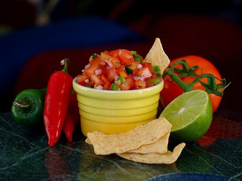 A bowl of fresh salsa, surrounded by some of the ingredients used to make it.