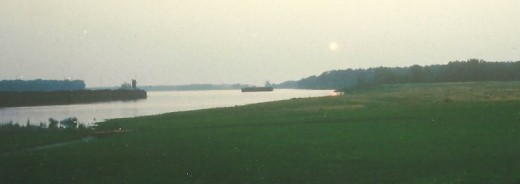 Two barges traveling up river towards a dam/lock area as the sun sets.