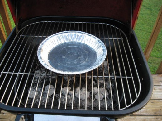 Image J - When your grill is not in use, place a clean aluminum pan onto the cooking grid so that it can catch rain that falls or seeps through the adjustable vent at the top of the hood.