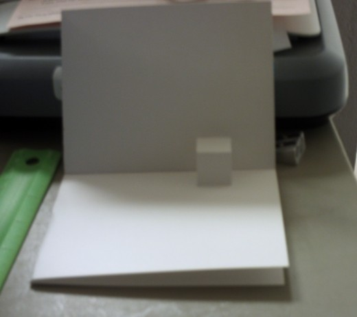 Fold the card back into a quarter fold and make the pop-up pop out by folding it along the top and bottom.