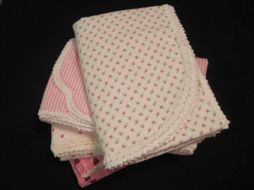Various shapes make a nice gift package of crochet edged baby blankets.