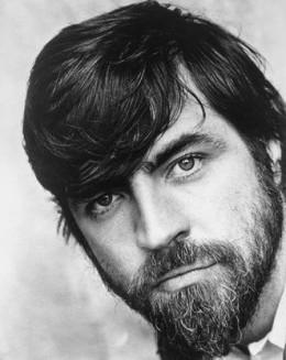 A younger Alan Bates, with beard.