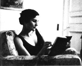 Nancy Mitford sitting with a book.