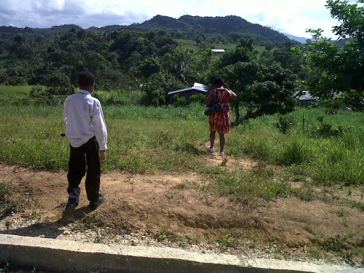 Son and wife taking path downhill to family home.  Photo by Glendon Caballero.