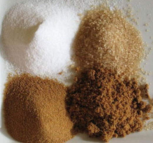 From top left, clockwise: white sugar, light brown sugar, dark brown sugar, rapadura sugar. Photo by Romain Behar | Wikimedia.