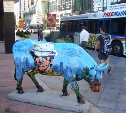 One of Denver's Famous Painted Cows with 16th Street Free Mall Ride in the background.